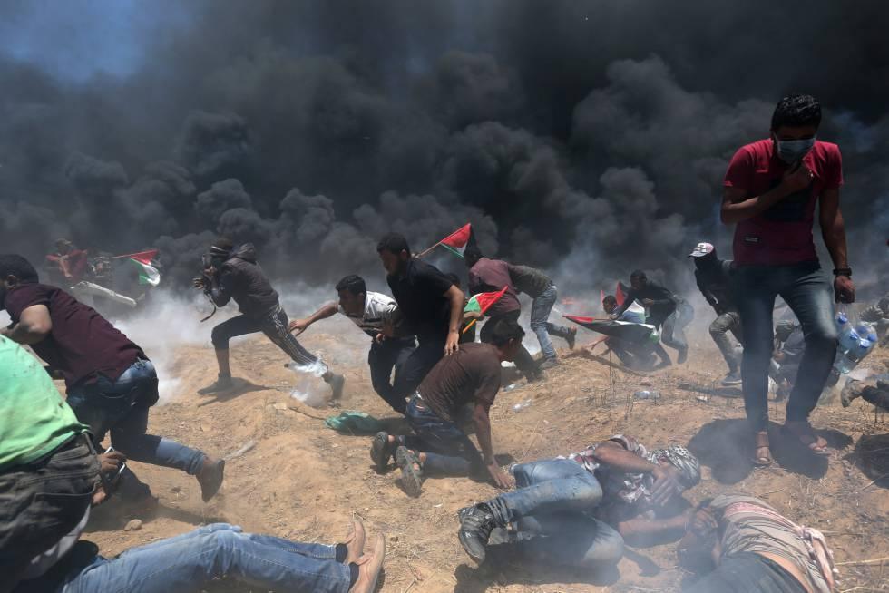 Un grupo de palestinos corren durante los enfrentamientos con las fuerzas de seguridad israelíes en la frontera entre Gaza e Israel, el 14 de mayo de 2018.