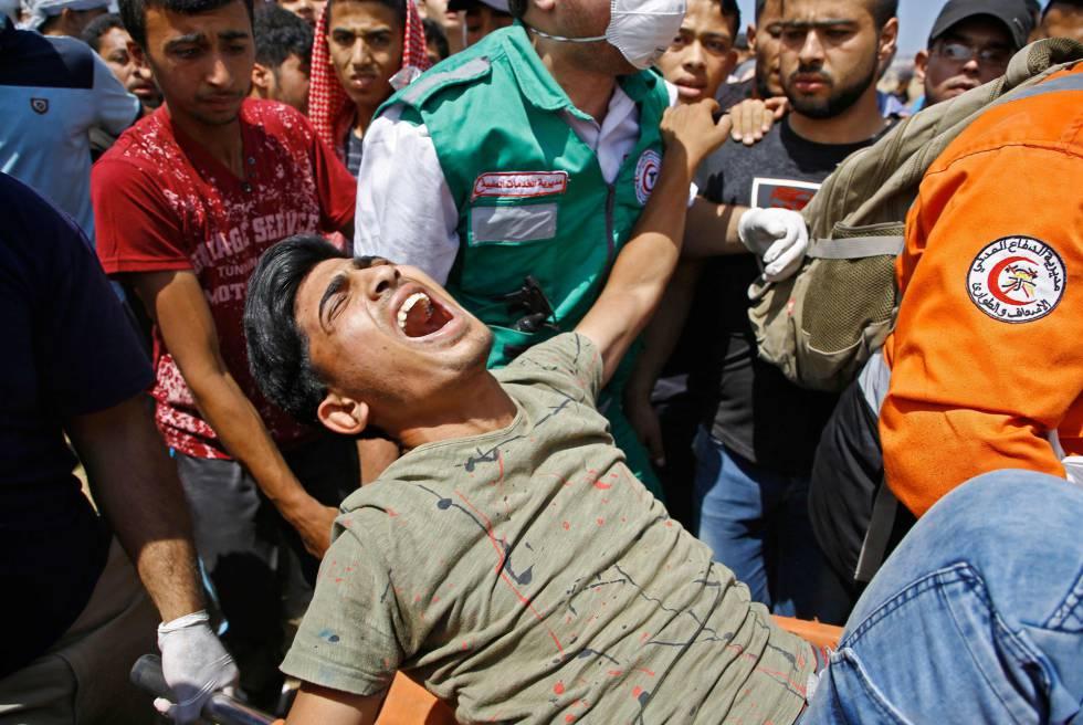 Personal de emergencias trasladan a un herido durante los enfrentamientos con las fuerzas de seguridad israelíes en la frontera entre Gaza e Israel, el 14 de mayo de 2018.