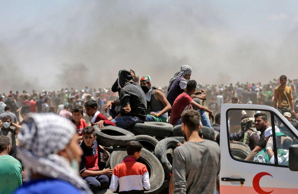 Un grupo de palestinos trata de incendiar neumáticos durante los enfrentamientos contra las tropas israelíes ceca de la franja de Gaza, el 14 de mayo de 2018.