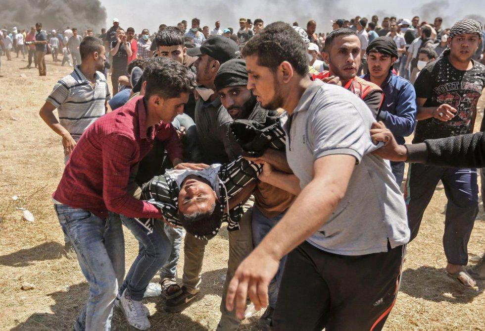 Un palestino herido es trasladado por otros manifestantes durante los choques entre palestinos y las tropas israelíes en la franja de Gaza, el 14 de mayo de 2018.