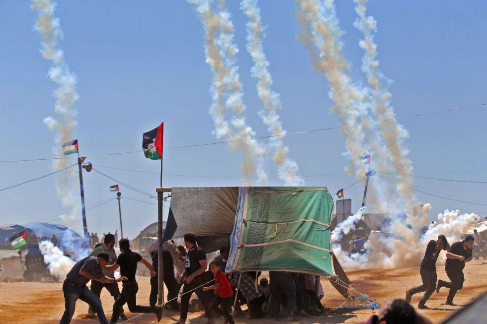 Un grupo de manifestantes palestinos se protegen del gas lacrimógeno lanzado por las tropas israelíes en la franja de Gaza, el 14 de mayo de 2018.