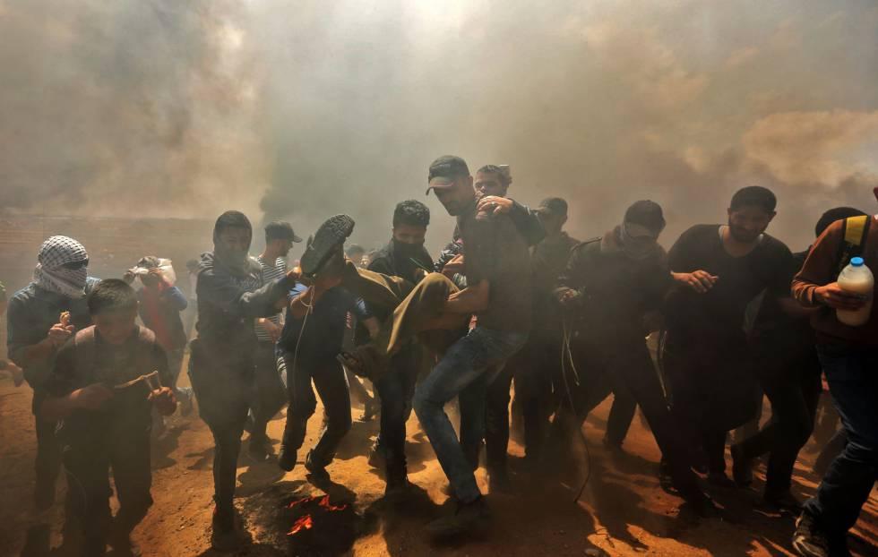 Palestinos trasladan a un herido durante los choques en la franja de Gaza, el 14 de mayo de 2018.