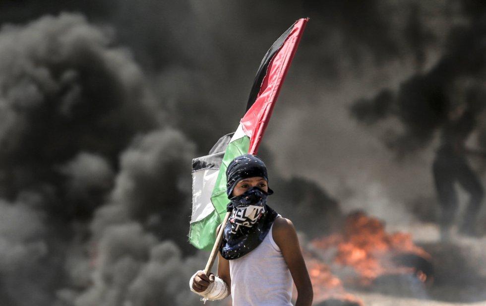 Un niño sujeta la bandera de Palestina durante los enfrentamientos en la franja de Gaza, el 14 de mayo de 2018.