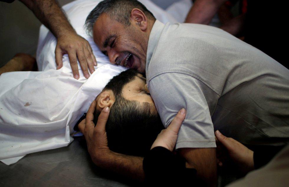 Shaher al-Madhoon, que murió durante la protesta en la frontera entre Israel y Gaza, y su hermano que reacciona por encima de su cuerpo en la morgue de un hospital en el norte de la franja de Gaza el 14 de mayo de 2018.