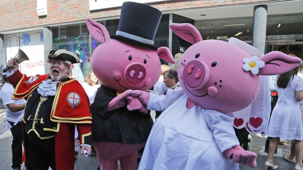 Un pregonero y una pareja de cerdos anuncian el cambio de nombre de la tienda Marks and Spence a Markle and Sparkle en Windsor.