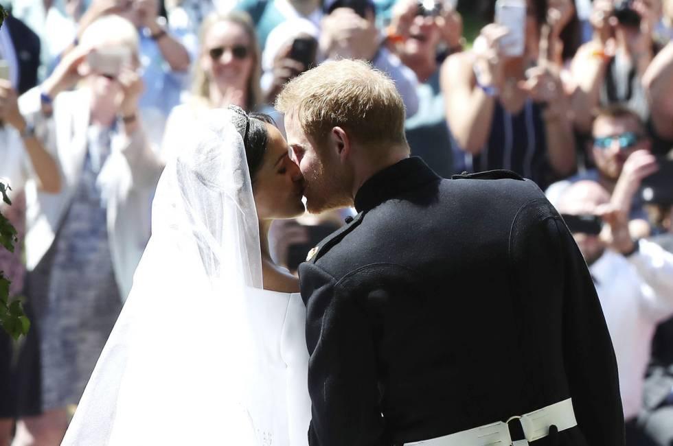 Los recién casados Enrique y Meghan se besana la salida de la capilla.