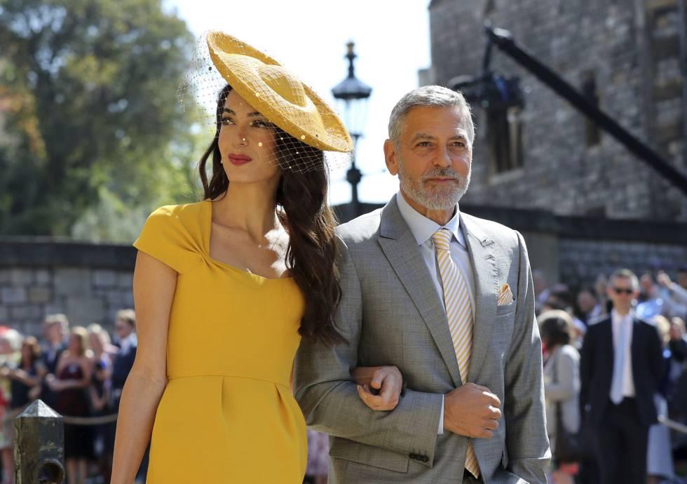 Amal y George Clooney llegan al castillo de Windsor. ella viste un impresionante vestido amarillo tocada con una pamela con redecilla. Él se ha decantado por un traje sencillo de color gris, que es el color que dicta el protocolo para las bodas de día.