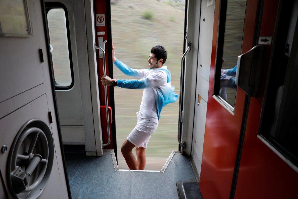 Sinan Usta, de 24 anos, posa para um selfie em uma porta aberta enquanto o trem segue seu caminho.