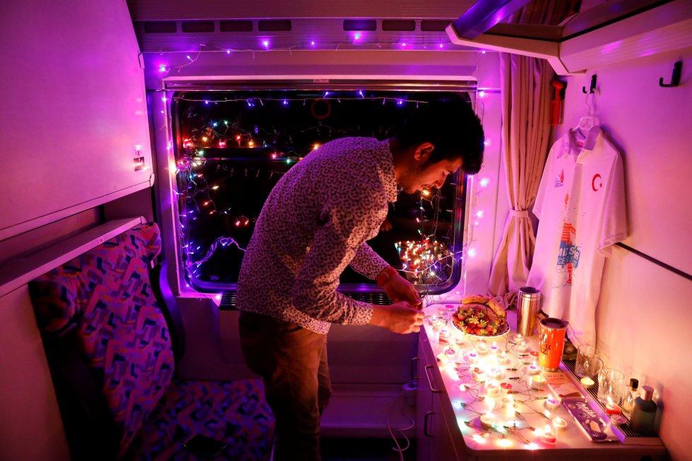 """Sinan Usta, estudante universitário de 24 anos, decora sua cabine com velas e luzes para lembrar a sua noiva. """"Tínhamos esta viagem preparada há meses, mas sua família não a deixou vir. Não gosto de deixar as coisas sem terminar, de modo que eu peguei o trem mesmo assim""""."""