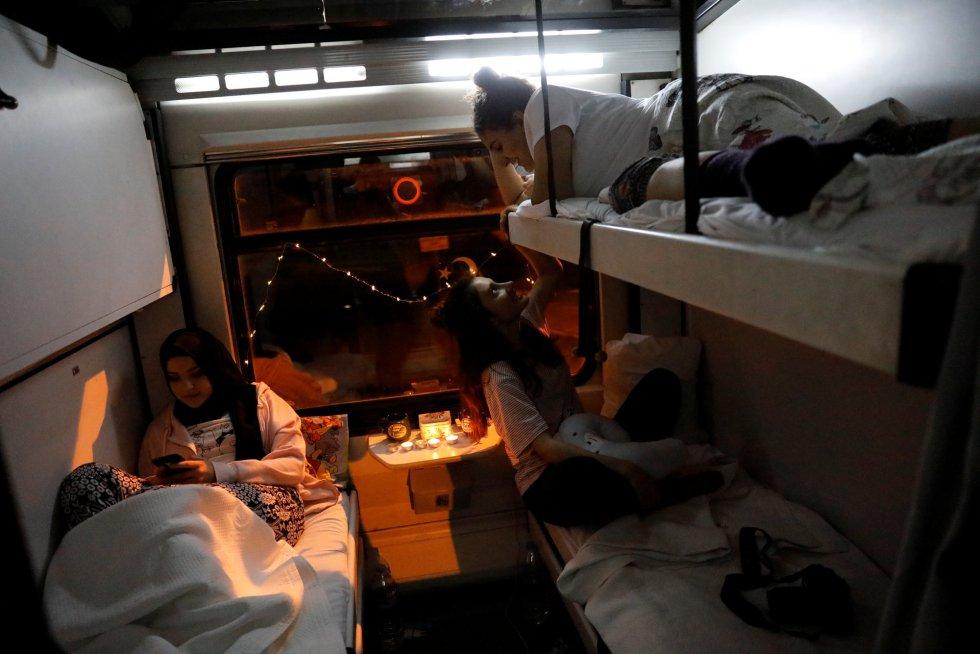 Busra Korkmaz (esq.), Ozlem Ozderya (dir.) e Berfin Abadan (acima) batem papo em sua cabine leito do Expresso do Leste enquanto o trem atravessa a província de Kayseri (Turquia).