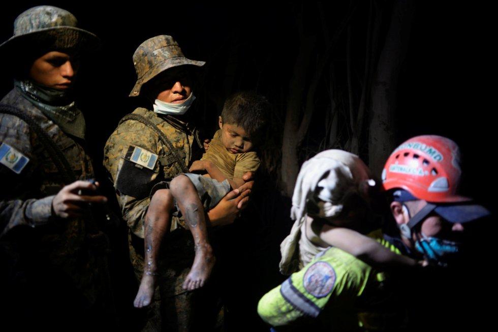 Un soldado traslada a un niño cubierto de ceniza a un hospital en El Rodeo, el 3 de junio.