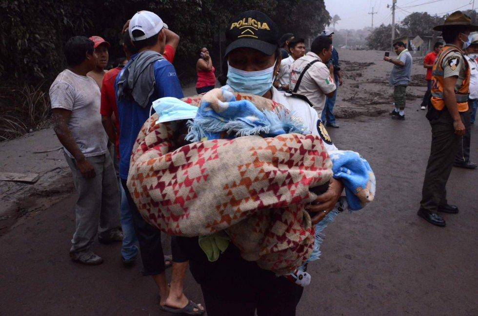 Un agente de policía traslada a un bebe después de la erupción en El Rodeo, el 3 de junio.