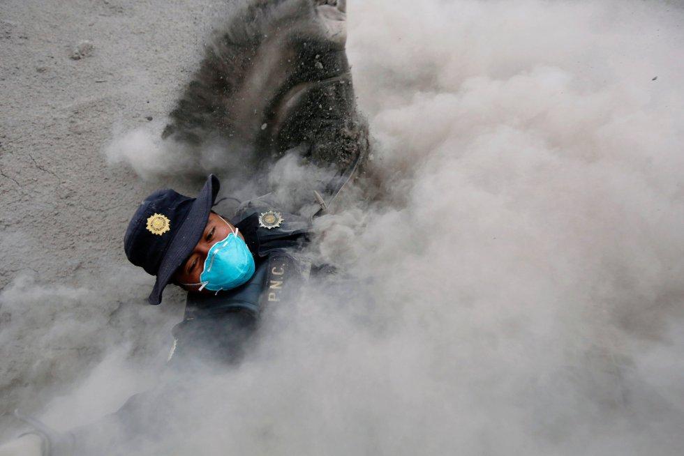 Un oficial de policía tropieza al escapar de un nuevo flujo piroclástico arrojado por el Volcán Fuego en la comunidad de San Miguel Los Lotes en Escuintla (Guatemala), el 4 de junio de 2018.