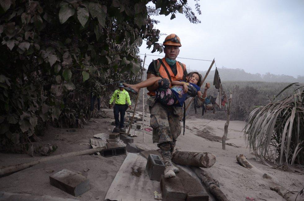 Un trabajador de los equipos de rescate de Guatemala ayuda a una niña en El Rodeo, Escuintla (Guatemala), el 3 de junio de 2018.