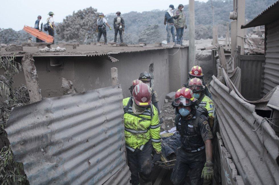 Un grupo de bomberos transporta a una víctima en la zona de Escuintla (Guatemala).