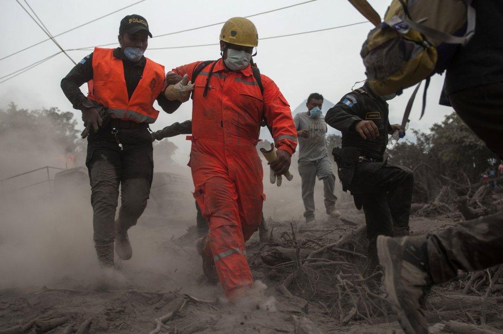 Bomberos y policías son forzados a evacuar una zona donde realizaban labores de rescate en Escuintla, (Guatemala).
