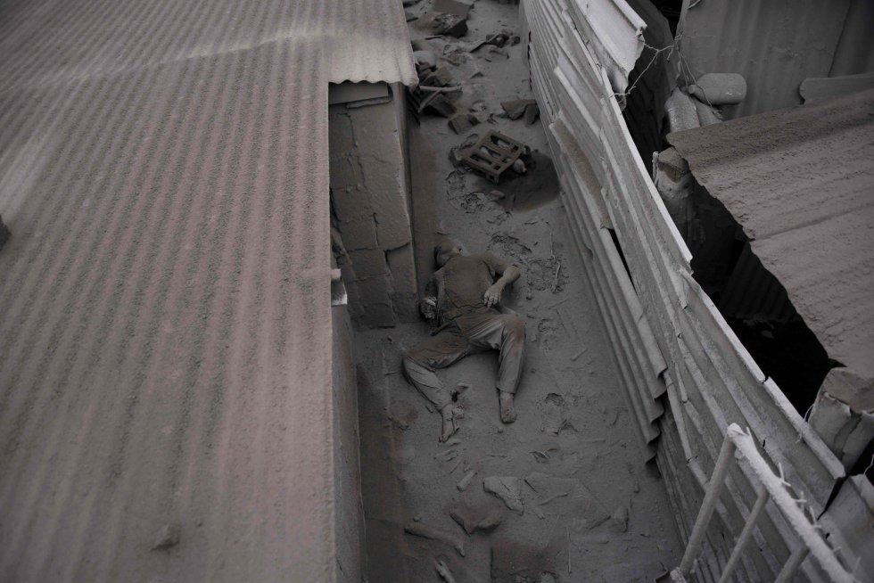 Una víctima yace en el suelo entre restos de ceniza lanzada por el volcán del Fuego, en San Miguel Los Lotes (Guatemala).