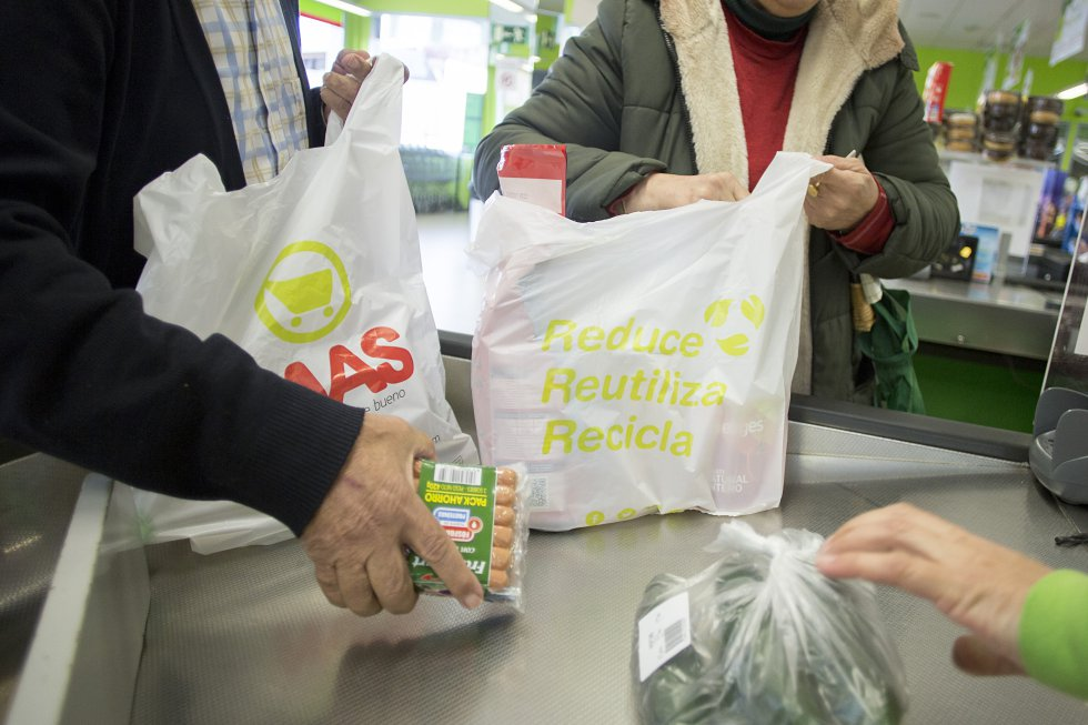 Unos clientes de un supermercado llenan bolsas de plástico con la compra, en Sevilla. Cada año se utilizan en el mundo cinco billones de bolsas plásticas desechables, según datos de la ONU.