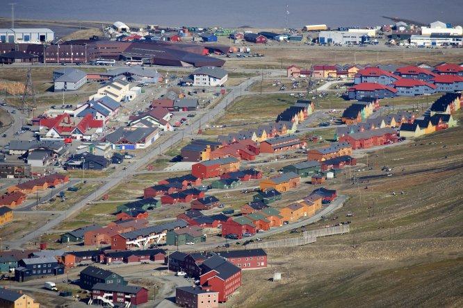 """""""El gobierno cede terrenos a todo el que lo solicita para que puedan construirse una casa. Les interesa que la ciudad esté habitada, por eso optar a una vivienda en Longyearbyen es tan sencillo"""", afirma el escritor Javier Reverte. Más de 2.000 habitantes están censados en la capital de Svalbard, archipiélago cuyo nombre proviene de un vocablo vikingo que puede traducirse como """"costa fría"""". A pesar de que conseguir una casa no es complicado ni caro, la vida en Longyearbyen no es apta para todos los públicos. Sobre todo para aquellos que busquen temperaturas cálidas y bullicio. En esta ciudad, el día polar, con unas temperaturas que no superan los 16 ºC, comienza el 20 de abril y termina el 22 de agosto. La noche polar comienza el 28 de octubre y acaba el 14 de febrero: durante estos meses las temperaturas son de -50 ºC y el sol no llega a salir. """"Se trata de una ciudad construida para sobrevivir en condiciones climatológicas extremas. Nada allí es bello o trascendente, sino sencillamente útil"""", explica Reverte."""