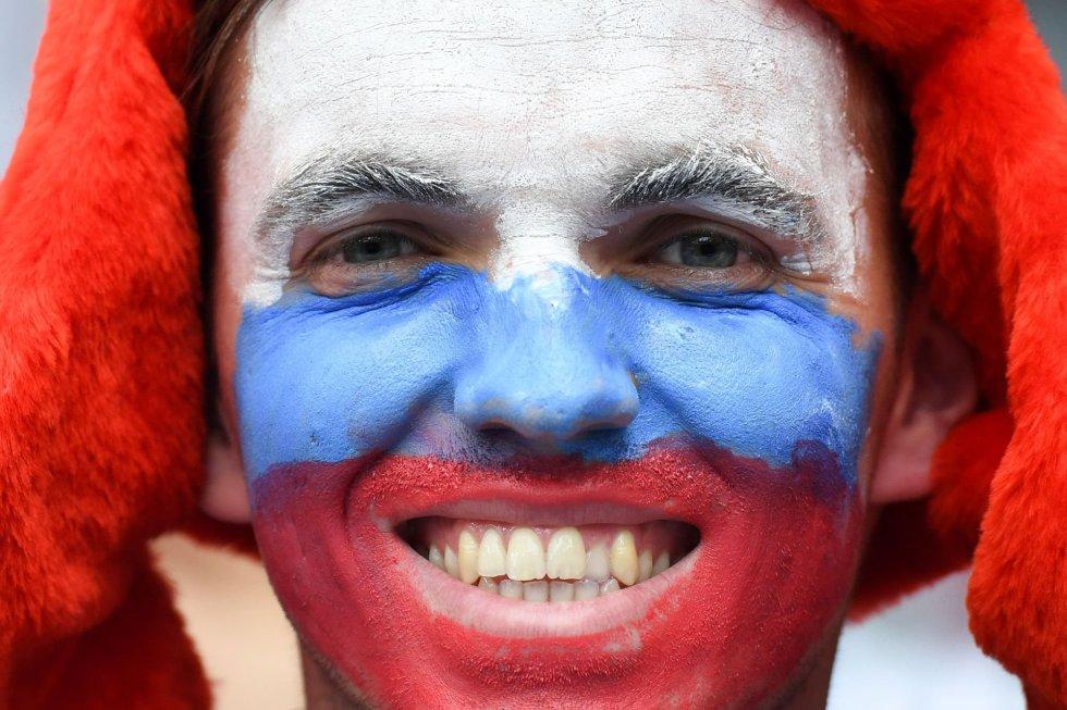 Un joven sonríe con la cara pintada de la bandera de Rusia antes de la ceremonia.