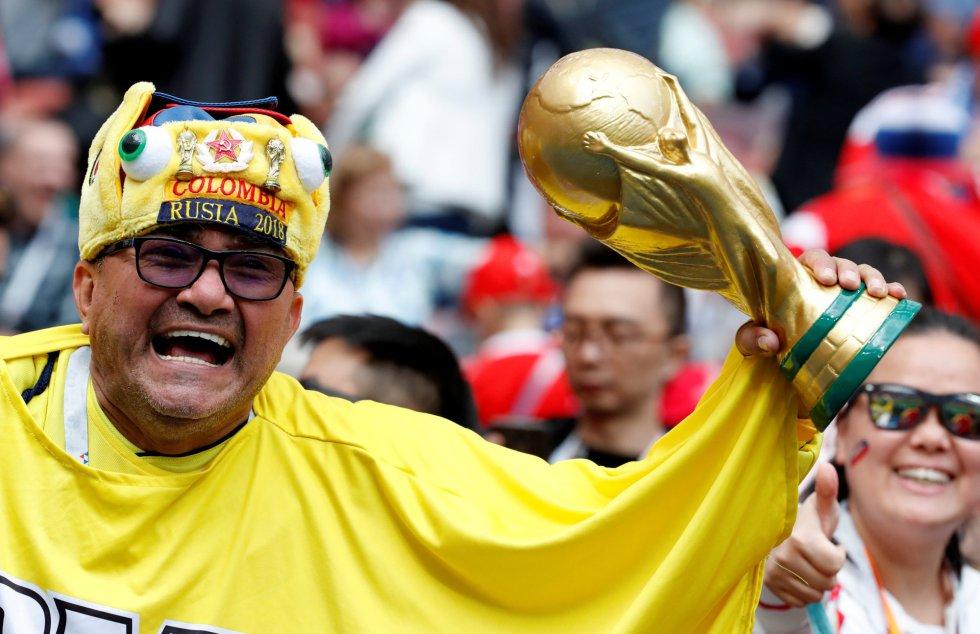 Un fan posa con una imitación de la copa antes del partido.