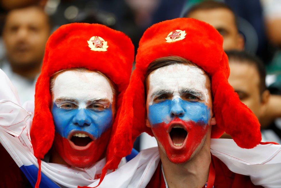 Dos seguidores con las caras pintadas con la bandera de Rusia esperan el inicio de la ceremonia.