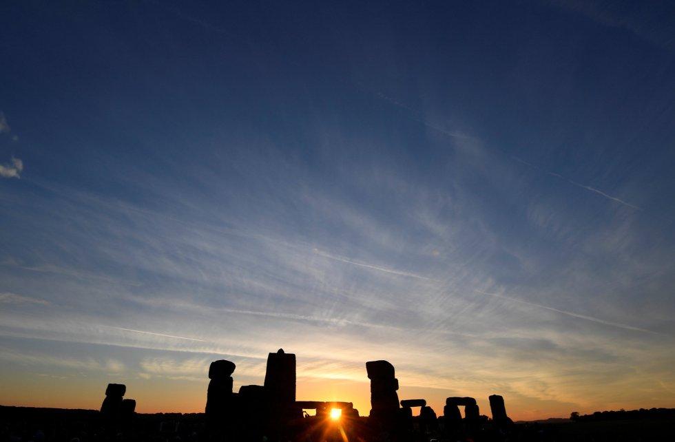 El sol sale entre las piedras del megalítico monumento de Stonehenge durante la celebración del solsticio de verano, en Salisbury (Reino Unido).