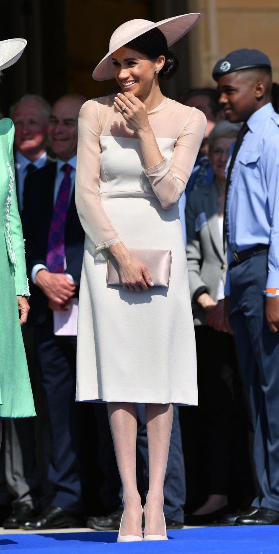 La primera aparición pública de Meghan de Sussex tras su boda fue en los festejos por el 70º cumpleaños del príncipe Carlos, el padre de su marido Enrique. Ese 22 de mayo optó por un vestido en color crema de la marca británica Goat con mangas transparentes que cuesta alrededor de 500 euros. Lo que más sorprendió de su atuendo es que llevara medias.