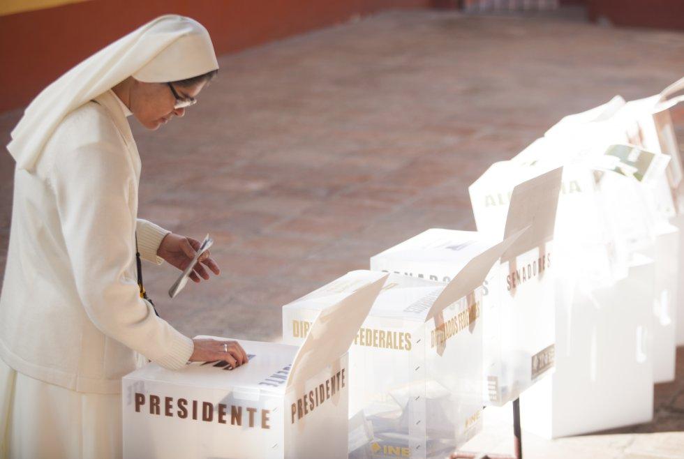 Una mujer religiosa  emite su voto en una casilla al sur de la ciudad de México. rn
