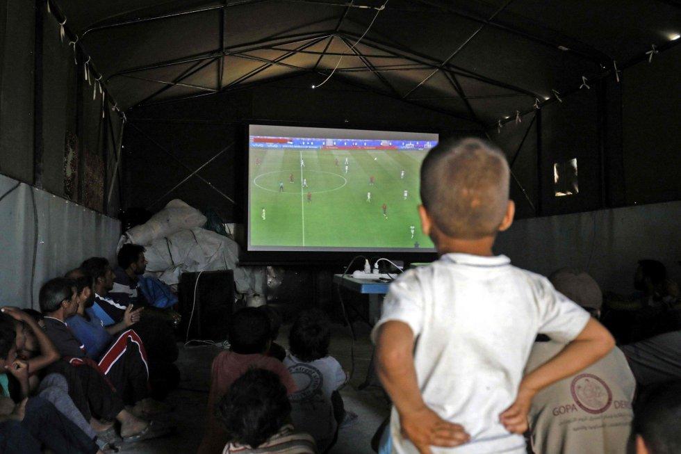 Desplazados sirios siguen un partido del Mundial de Rusia 2018 desde el campamento de desplazados de Ain Issa en Raqqa (Siria), el 17 de junio de 2018.