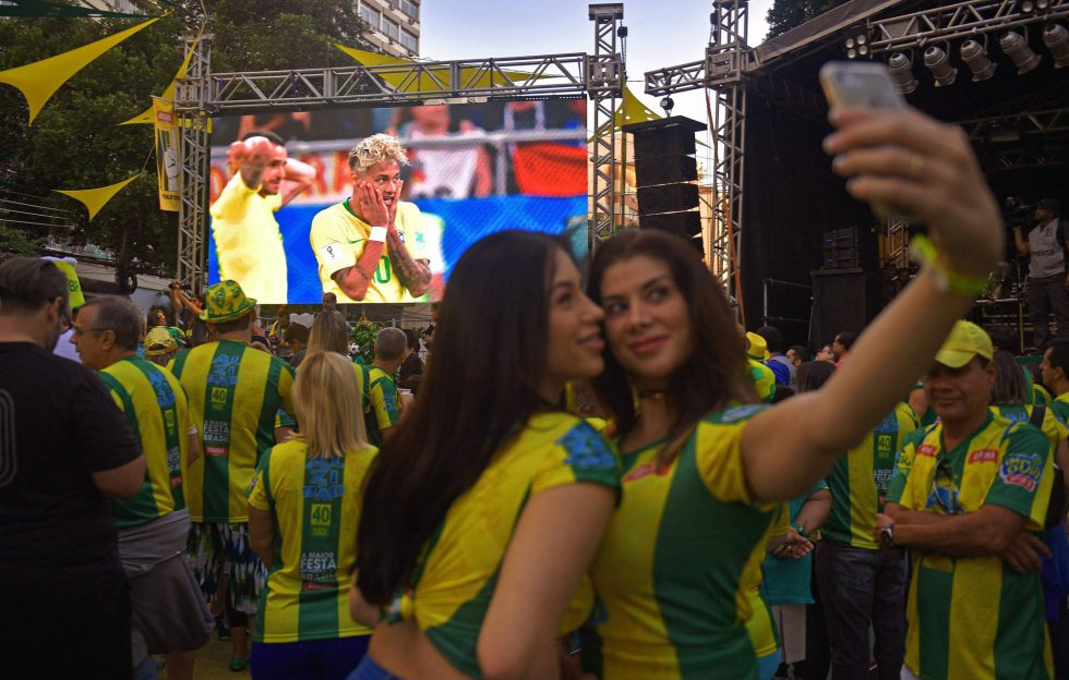 Dos chicas se hacen un selfie mientras siguen el partido entre Brasil y Suiza desde una pantalla gigante instalada en un barrio de Río de Janeiro, el 17 de junio de 2018.