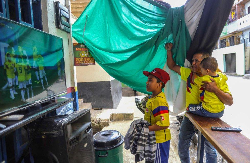 Una familia sigue el partido entre Colombia y Senegal en una televisión en la Comuna Popular 1 de Medellín (Colombia), el 28 de junio de 2018.