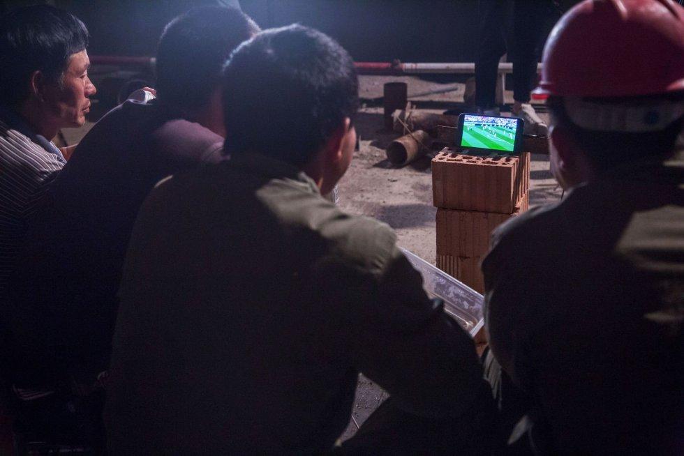 Trabajadores chinos ven el partido de fútbol entre Portugal y Marruecos desde un teléfono móvil en Hangzhou (China), el 20 de junio de 2018.