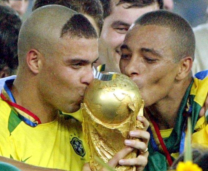 30 de junio de 2002. Los brasileños Ronaldo, izquierda, y Kléberson besan la Copa del Mundo tras ganar 2-0 a Alemania en la final jugada en el estadio Internacional de Yokohama (Japón). Brasil, derrotada por Francia en la final de 1998, se imponía ante una estupenda Alemania con dos goles de Ronaldo. La 'canariha' conseguía su quinto título.