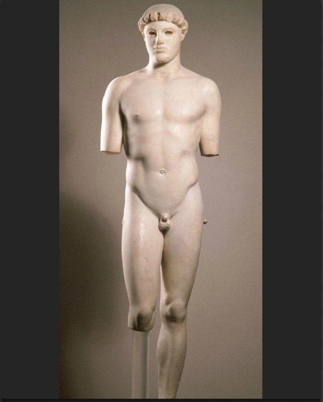 """¿Pero qué hace este hombre desnudo? Se trata de la primera estatua griega en emplear el 'contrapposto', ese efecto por el que el peso se carga en una sola pierna, aportando vida y movimiento a la figura. El típico motivo del efebo desnudo realizaba así un avance técnico fundamental. Luego vendrían los otros a cargo de Policleto, Lisipo o Praxíteles. ¿Por qué es tan bueno? El especialista en arte David Trullo tiene sus preferencias en lo que a estatuaria griega se refiere, pero destaca lo revolucionario de esta obra: """"Me siguen gustando más los arcaicos, aunque este es fascinante: emerge de la piedra, y empieza a moverse. Ese incipiente 'contrapposto' que hará que ya nada sea lo mismo…""""."""