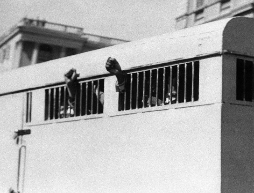 El 16 de junio de 1964, ocho hombres, entre ellos el líder antiapartheid y miembro del Congreso Nacional Africano (ANC), Nelson Mandela, fue sentenciado a cadena perpetua en el juicio de Rivonia. Abandonan el Palacio de Justicia en Pretoria con los puños en alto a través de las ventanas con barrotes del automóvil de la prisión.