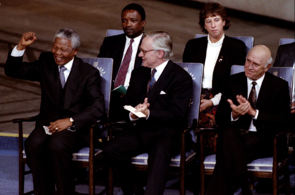 Nelson Mandela (esquerda) ergue o punho após a atuação da banda sul-africana Ladysmith Black Mombasa, durante a cerimônia de entrega do Prêmio Nobel da Paz em Oslo, em 1993.