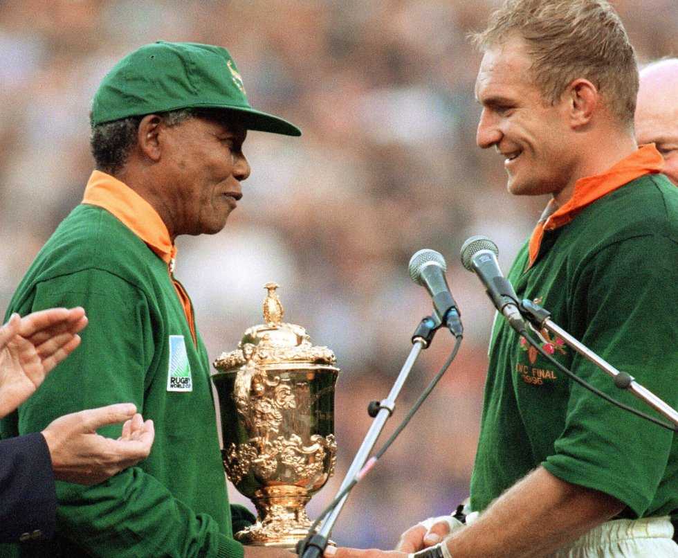 """Nelson Mandela entrega o troféu ao capitão da equipe de rugby, Francois Pienaar, após a vitória contra a Nova Zelândia (por 15-12), na final da Copa do Mundo de Rugby de 1995, em 24 de junho, no Ellis Park de Johannesburgo. Mandela vestiu a camiseta da seleção nacional e converteu-se em talismã de sua equipe, que ganhou um campeonato do qual não pôde participar durante anos pela vigência do """"apartheid""""."""