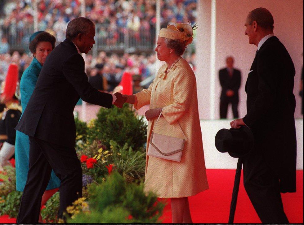 El presidente de Suráfrica, Nelson Mandela (i), estrecha la mano de la reina Isabel II de Inglaterra durante una parada de la Guardia a caballo en Londres, en su primera visita oficial a Reino Unido, el 10 de julio de 1996. A la derecha, el príncipe Phillip y la princesa Anne junto a Mandela. rn