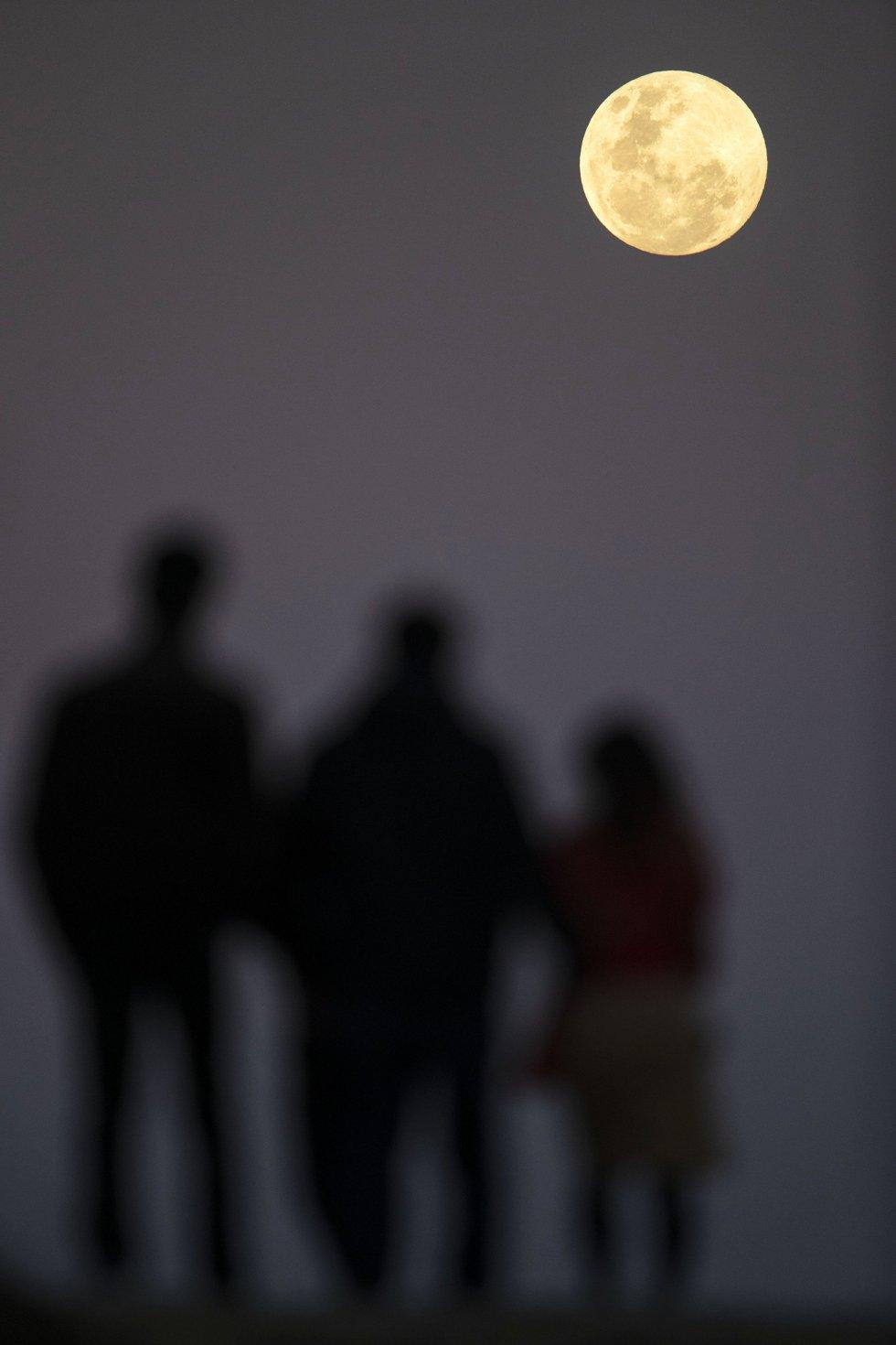 La luna llena se eleva cerca de la playa de Bondi de Sídney antes del eclipse lunar.