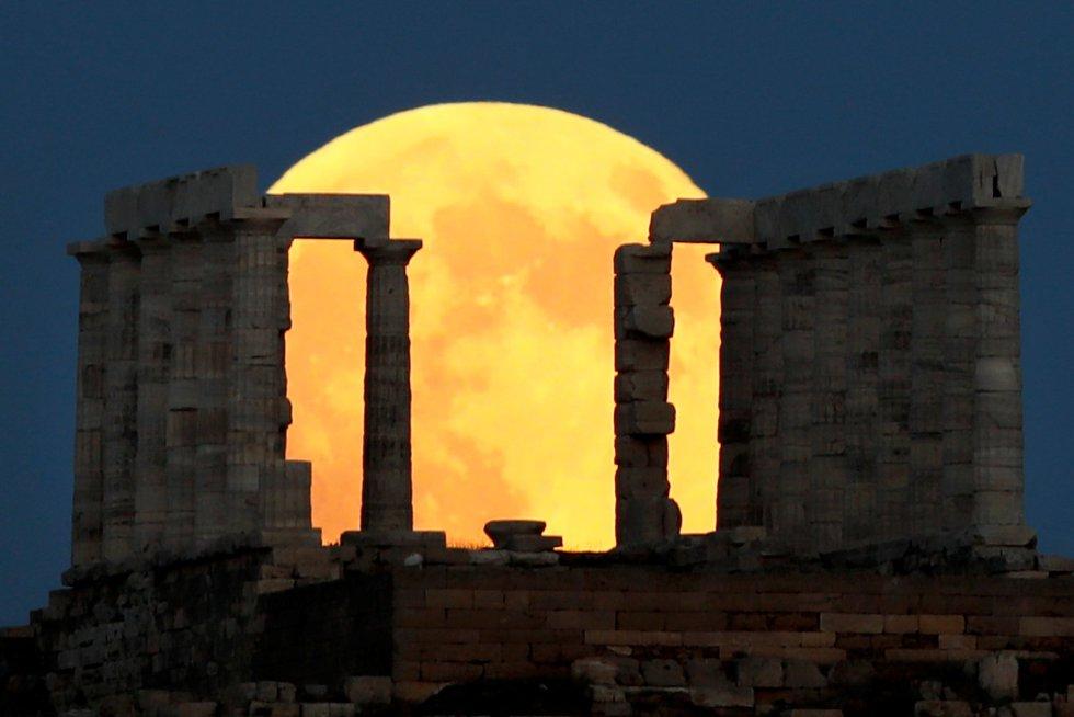 Una luna llena se levanta detrás del Templo de Poseidón antes del eclipse lunar en el Cabo Sounion, cerca de Atenas, Grecia, el 27 de julio de 2018.
