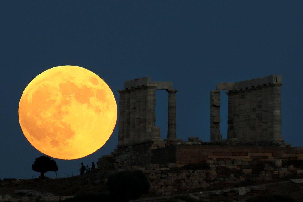 Una luna llena se levanta detrás del Templo de Poseidón antes de un eclipse lunar en el Cabo Sounion, cerca de Atenas, Grecia.