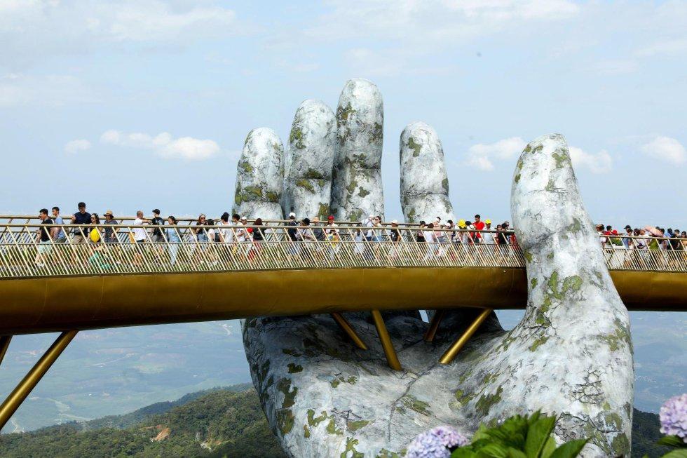 Varios turistas cruzan el nuevo puente Cau Vang (puente de oro).