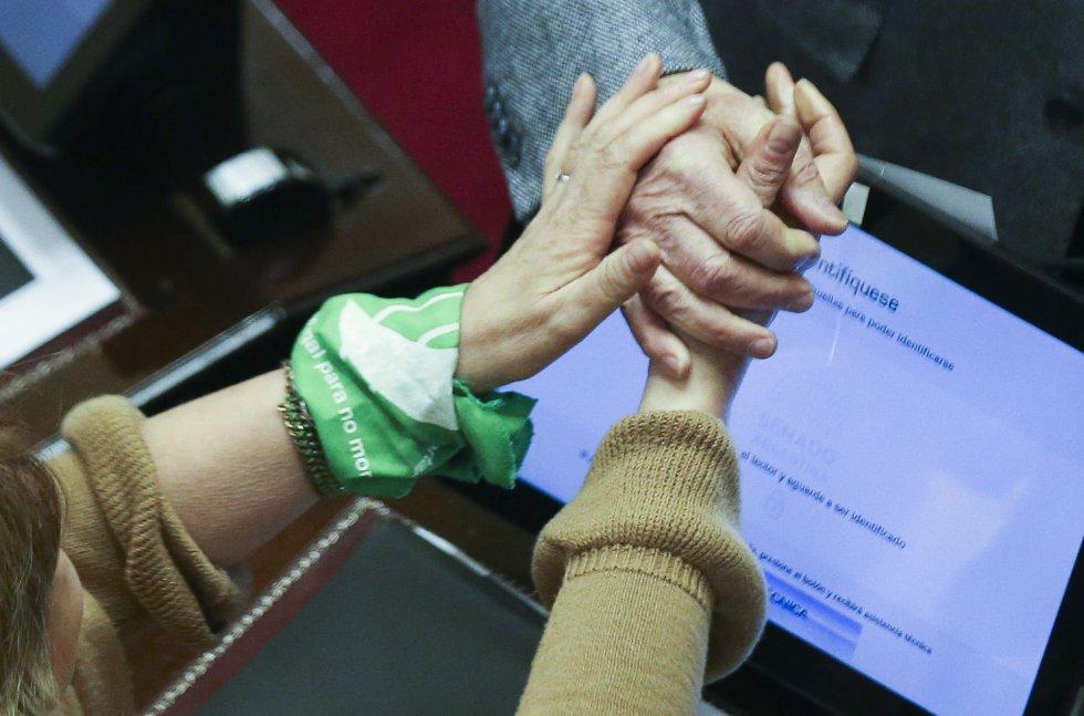 Una senadora con un pañuelo verde en apoyo a la legalización saluda a otro senador durante la sesión para debatir el proyecto de ley en Buenos Aires (Argentina).