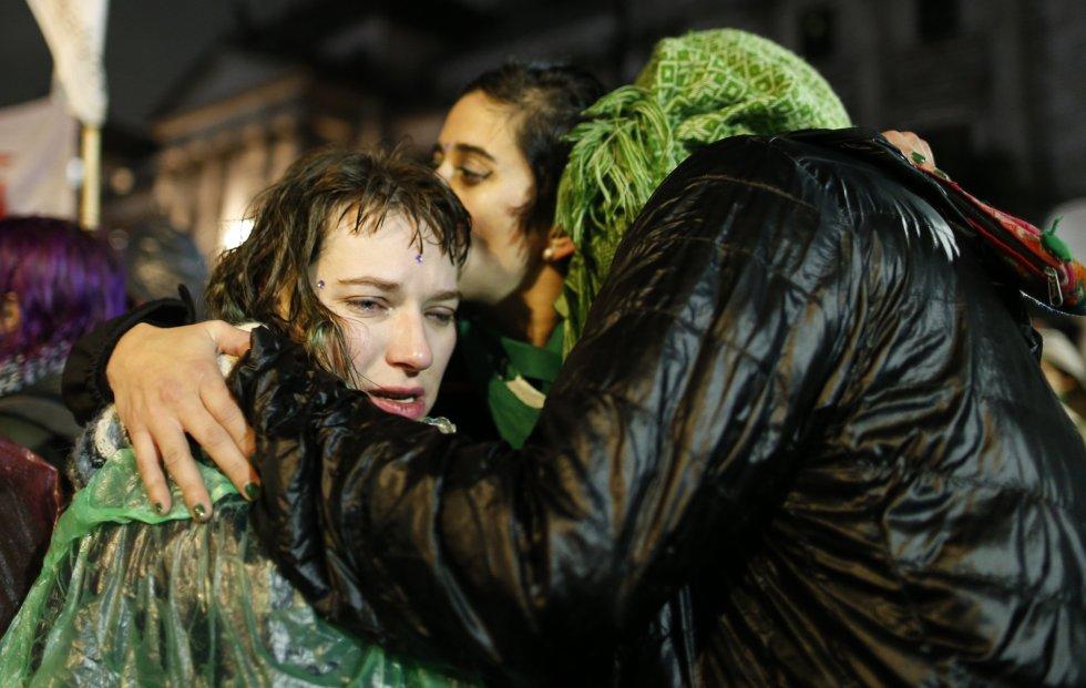Dos jóvenes a favor de la ley del aborto se abrazan en el exterior del Senado para mostrar su apoyo.