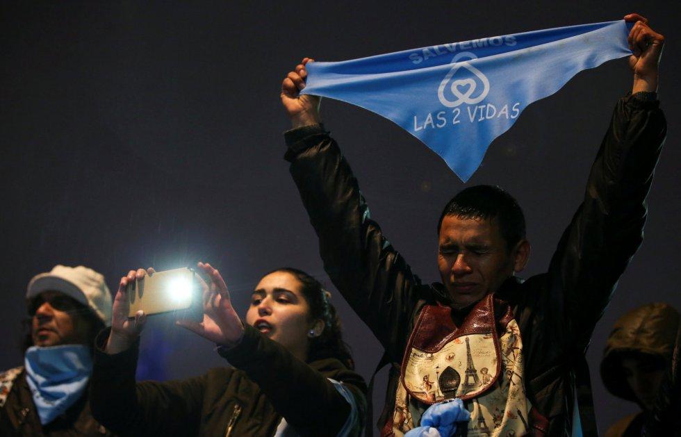 """Un manifestante contra la despenalización del aborto sostienen un pañuelo que dice """"Salvemos las dos vidas"""" frente al Senado en Buenos Aires."""