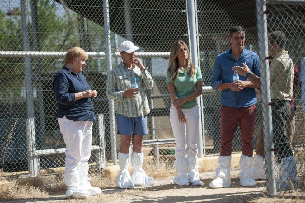 Angela Merkel, Joachim Sauer, María Begoña Gómez Fernández y Pedro Sánchez escuchan las explicaciones de los trabajadores del centro.