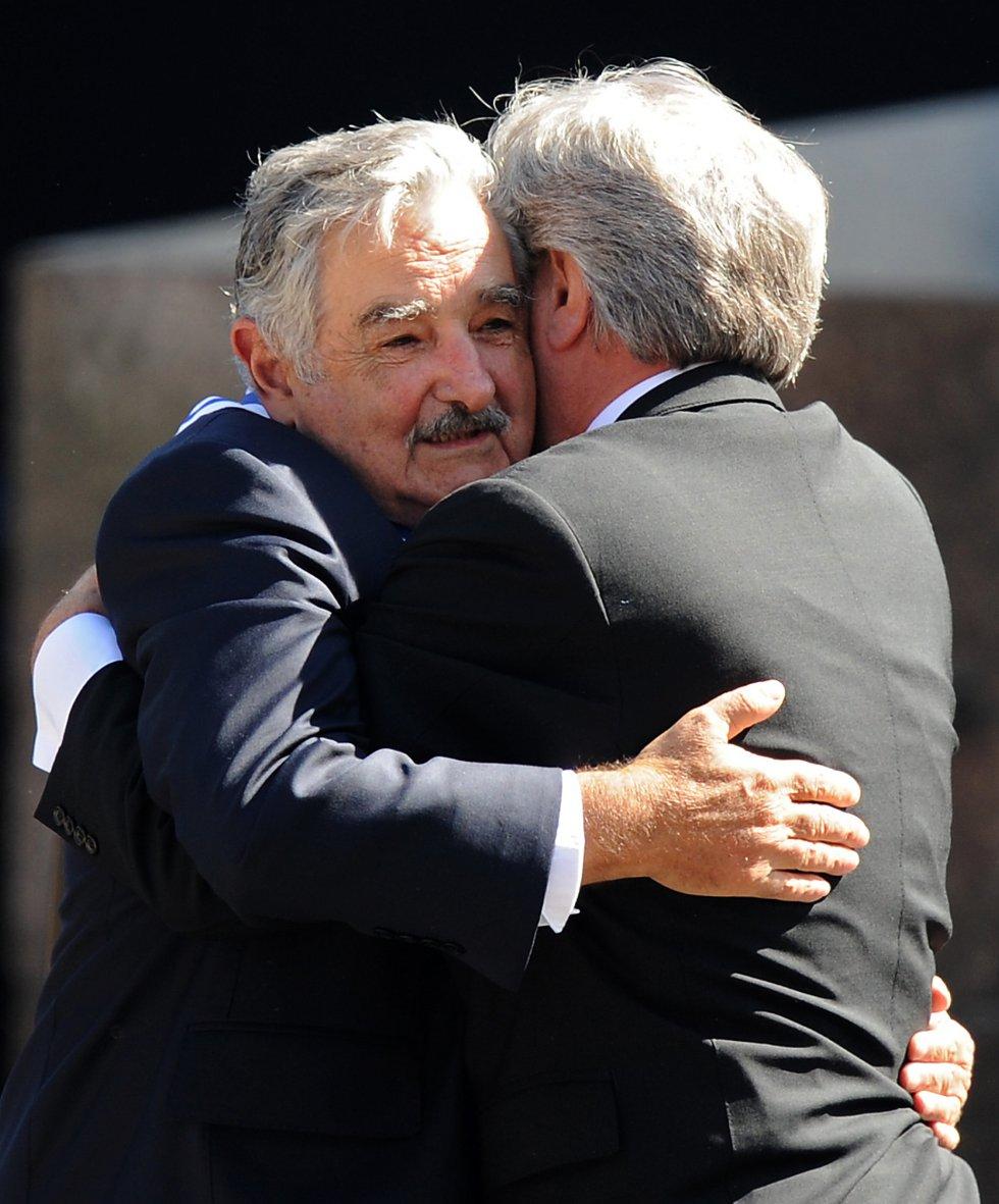 """El flamante presidente uruguayo, José """"Pepe"""" Mujica (izquierda) abraza al mandatario saliente Tabaré Vázquez en el acto de sucesión entre ambos. Mujica recibió la faja ceremonial en Montevideo el 1 de marzo de 2010."""