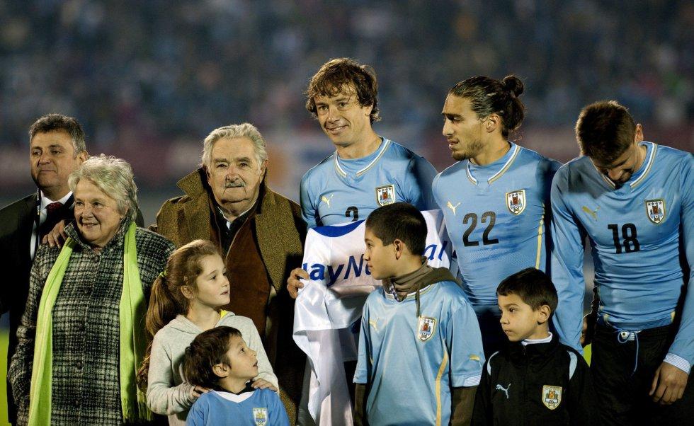 El presidente uruguayo José Mujica y su esposa Lucia Topolansky, junto a los futbolistas uruguayos Diego Lugano, Martín Cáceres y Néstor Ramírez (de izquierda a derecha), antes del inicio del partido de fútbol amistoso contra Eslovenia en el Estadio Centenario Montevideo, el 4 de junio de 2014.