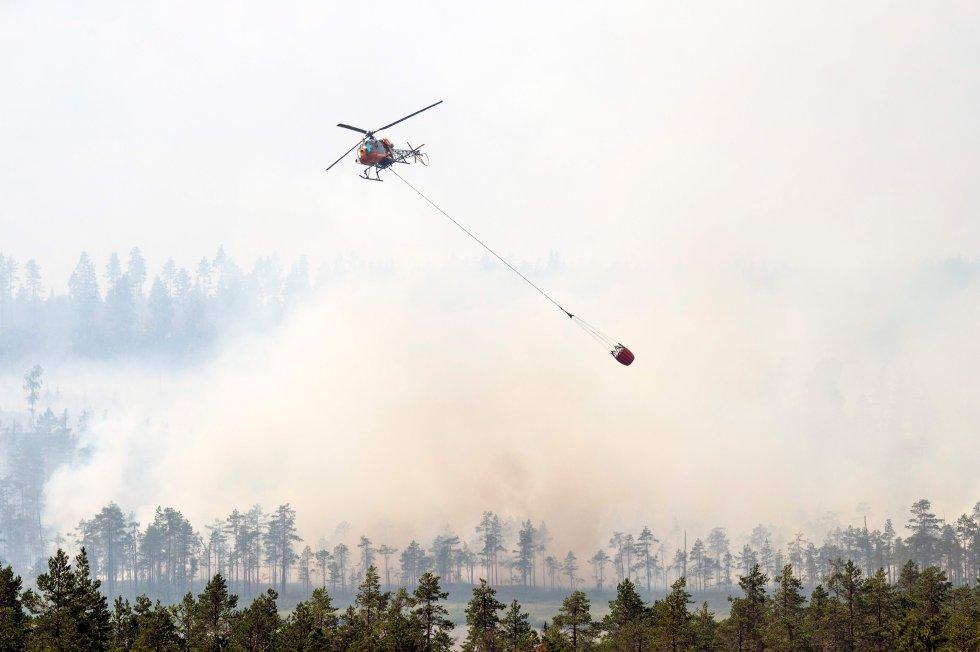 El norte de Europa también es víctima de las sequías. La ola de calor y las escasas precipitaciones han provocado incendios en el Círculo Polar Ártico. En julio de este año, Suecia se ha visto obligada a solicitar ayuda internacional por una oleada de fuegos. En la foto, los bomberos usan helicópteros para atacar las llamas en un bosque en Korskrogen, cerca de Ljusdal (Suecia), el 25 de julio de 2018.